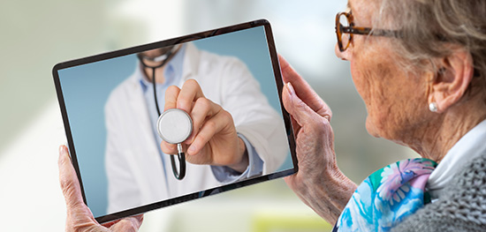 Senior woman consults a e-health doctor with tablet computer sit
